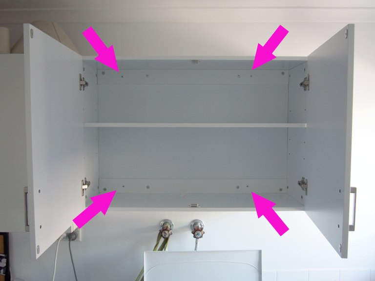 The arrows point to the screws attaching the cupboard to the battens